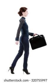 Elegant businesswoman in black suit and handbag walking side view on white studio background