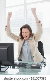 Elegant businesswoman cheering with hands raised and eyes closed in office