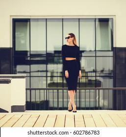 Elegant businesswoman in skirt pencil and sunglasses