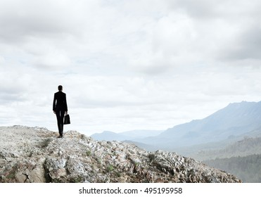 Elegant businesswoman standing on rock top and looking ahead