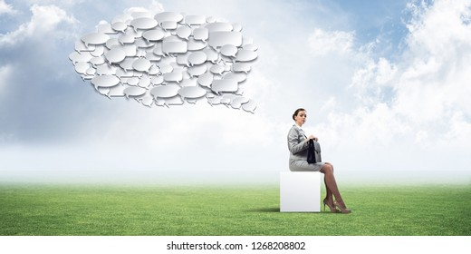 Elegant businesswoman with suitcase in hand sitting on white cube and many chat icons