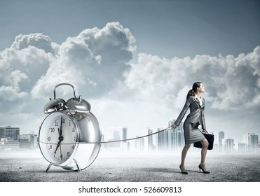 Elegant businesswoman with suitcase holding alarm clock on lead - Shutterstock ID 526609813