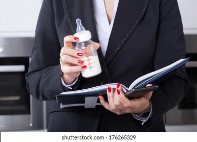 An elegant businesswoman working while holding her child's milk bottle