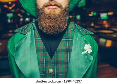 Elegant and calm young man in pub. He wear green suit of saint patrick. Guy has red beard.