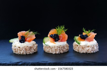 Elegant canapes with smoked salmon and black caviar on whole grain patties over black slate platter.