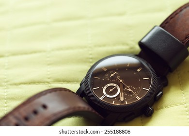 Elegant casual brown watch on green background. Vintage effect.