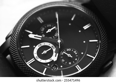 Elegant casual brown watch on green background. Black and white photo.
