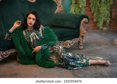 elegant caucasian girl in a luxurious long sequins lace dress with a green fluffy boa in her hands posing in the retro room with vintage luxury furniture