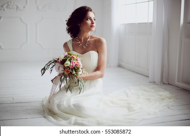 Elegant charming young brunette bride is sitting on white rustic wooden floor in a wedding dress with a big bouquet of flowers, daydreaming, in the interior Waiting for groom. detailed retouch