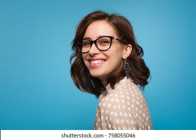 Elegant cheerful brunette in eyeglasses smiling at camera on blue background.
