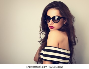 Elegant chic female model with long hair posing in fashion sunglasses in striped dress on toned color background. Closeup portrait with empty copy space
