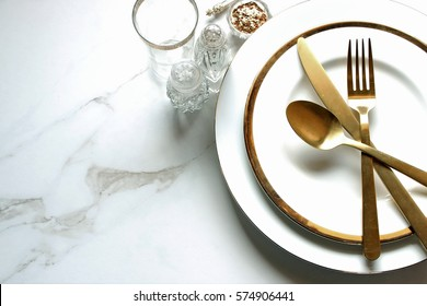 Elegant and chic gold and white table setting with empty white marble space for copy.