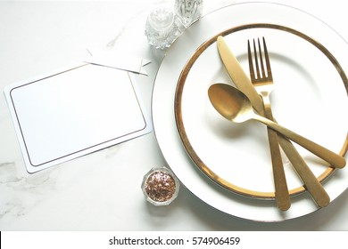 Elegant and chic gold and white table setting with blank note card for copy.