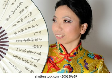 Elegant Chinese lady wearing traditional colorful dress. Kind female model from Asia holding fan in her hand.