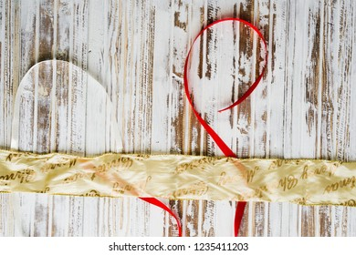 Elegant Christmas ribbon golden and red with text merry christmas over a rusty wooden white background, fla lay top viewcomposition