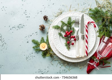 Elegant christmas table setting design captured from above (top view, flat lay). White plates, glass, cutlery (silverware), candy cane and decorations. Background layout with free text (copy) space.