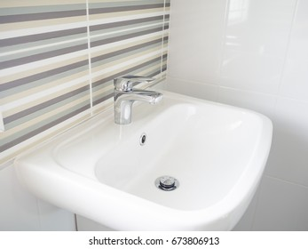Elegant chrome faucet on clean and brilliant white sink.