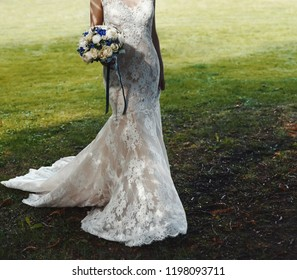 Elegant and classy wedding dress, bride is posing with a boquet