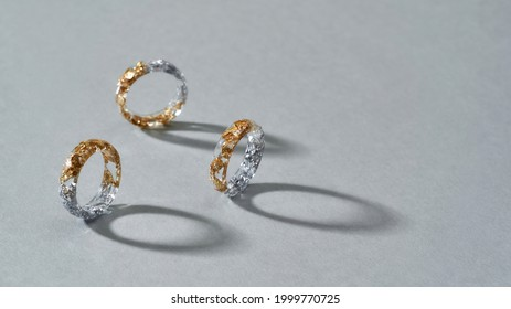 Elegant clear resin rings with half golden and silver filling standing on gray background, widescreen. Jewelry fashion photography