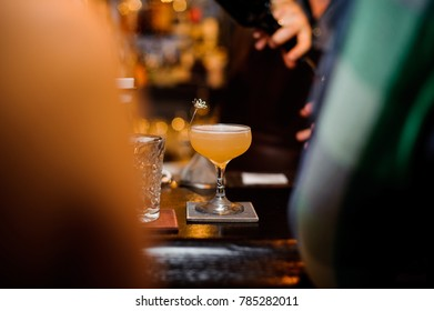 Elegant cocktail glass with alcoholic drink on the bar counter against the blurred background of bar hall