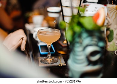 Elegant cocktail glass filled with alcoholic drink on the bar counter against the blurred background of bar