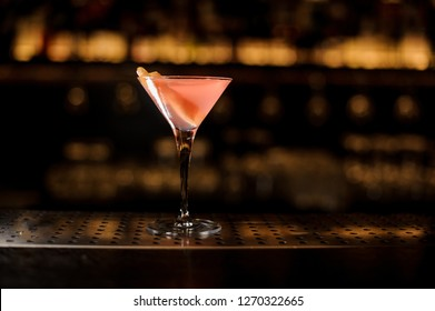 Elegant cocktail glass filled with sweet and tasty pink alcoholic drink decorated with orange