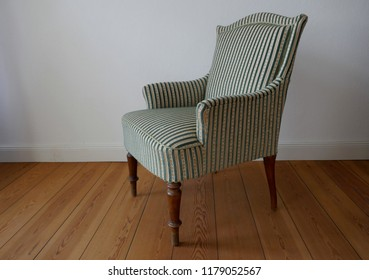 Elegant, comfortable armchair with armrests in front of white wall.. Retro style. Velour, green, beige, gold, striped.