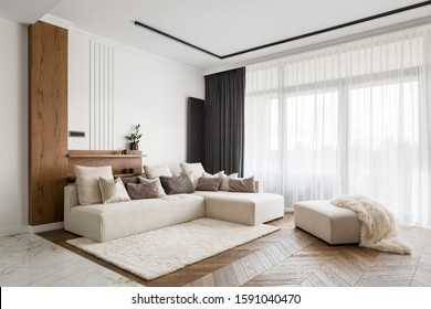 Elegant and comfortable designed living room with big corner sofa, wooden floor and big windows