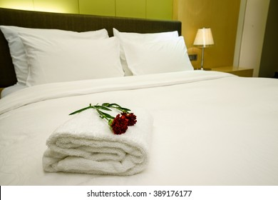 Elegant and comfortable home & hotel bedroom interior as background, the red carnation flowers and bath towel at bed, romantic style.