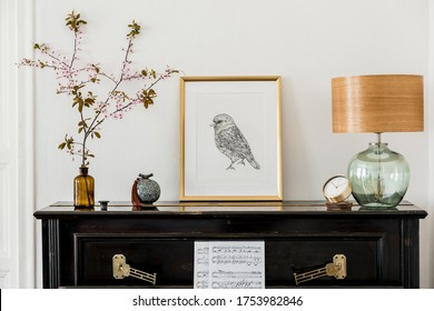 Elegant composition at living room interior with black piano, gold mock up poster frame, spring flowers, decoration, lamp and stylish presonal accessories in modern home decor.