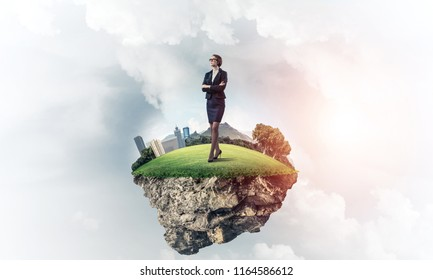 Elegant confident businesswoman standing on green floating island in blue sky