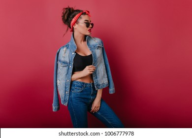 Elegant confident girl with vintage hairstyle enjoying photoshoot. Studio portrait of romantic brunette young woman wears jeans.