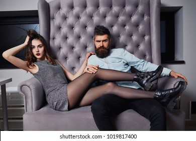 Elegant couple. Beautiful young couple in formal wear looking at the camera while sitting in a couch together. Luxury fashionable couple in tender passion. Beautiful woman near the man. beauty girl