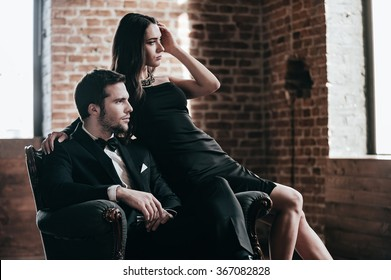 Elegant couple. Beautiful young couple in formalwear looking at the window while sitting in a chair together