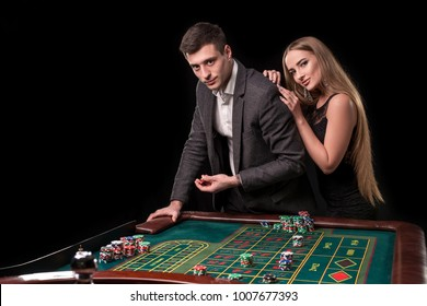 Elegant couple at the casino betting on the roulette, on a black background