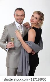Elegant couple celebrating with champagne on white background