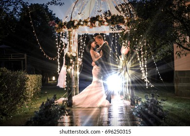 Elegant couple embracing in illuminated gazebo at night