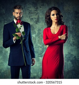 Elegant couple in evening dress portrait. Man gives rose to woman and she is looking aside. Focus on woman.