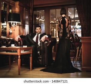Elegant couple in formal dress in luxury cabinet