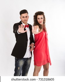 elegant couple gesturing stop with hands up, light background