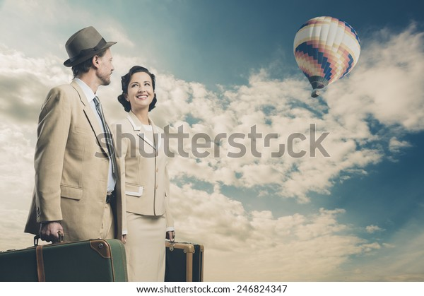Elegant couple leaving for vacations with luggage and hot air balloon, 1950s style