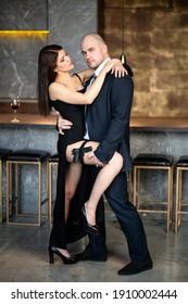 Elegantes Paar in Liebe. Ein Mann in einem Anzug und eine Frau mit einer Pistole in einem schwarzen Kleid mit einem Slit, Loft. Ein Typ und ein Mädchen umarmen sich in einem Restaurant. Valentinstag