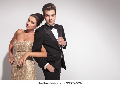 Elegant couple posing while holding arms, both looking at the camera.