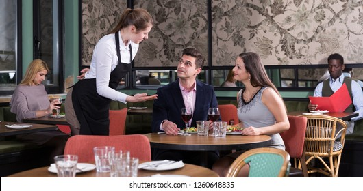 Elegant couple sitting at restaurant table talking with young waitress
