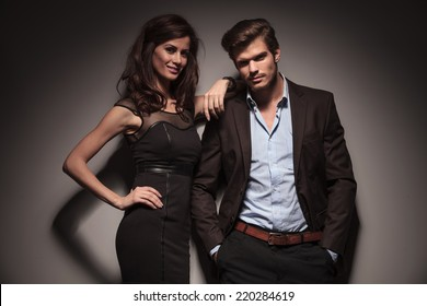 Elegant couple smiling and looking into the camera, the woman is leaning on her boyfriend while he is leaning on the wall with his hand in pocket.