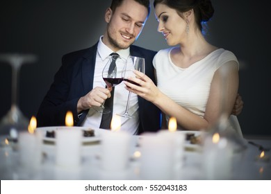 Elegant couple toasting each other with red wine