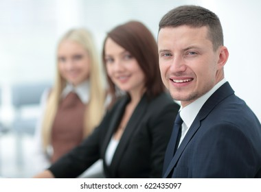 Elegant co-workers looking at camera during meeting in office