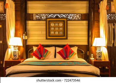 Elegant and cozy bedroom with set of vintage twin pillows on headboard and coverlet on white king size bed with wall decoration, beautiful flame warm light illumination