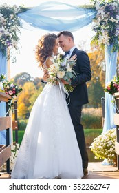 Elegant curly bride and happy groom outdoors on the background the lake. Creative stylish wedding ceremony