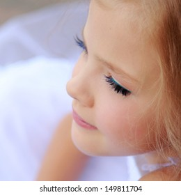 Elegant cute little girl with makeup in a white dress with beautiful hair